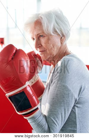 Concentrated senior active female in boxing gloves going to hit rival while fighting during preparation for sports competition