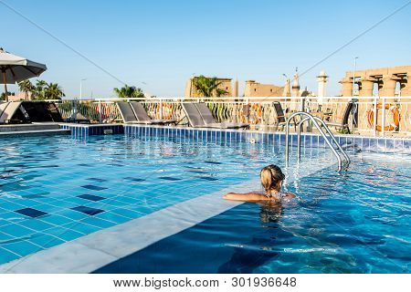 Young Beautiful Woman Sunbathing In Swimming Pool At Luxurious Looking On Sunshade Parasol In Egypt
