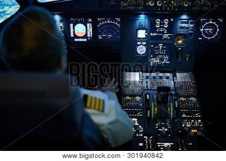 Rear View Of Unrecognizable Pilot Sitting At Control Panel With Radar Devices And Flight System Butt