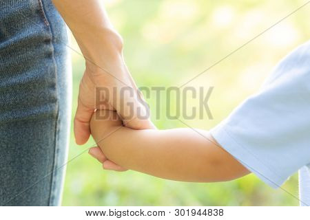 Closeup Mother Or Parent And Son Holding Hand With Love Together In Summer Outside In The Park, Mom