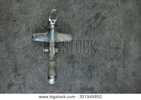 Water-tap On The Gray Concrete Wall . Copy Space. Top View.