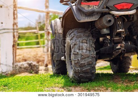 Atv Quad Bike Vehicle Standing Near Wooden Fence At Farm Or Horse Stable. Back View Of All Wheel Dri