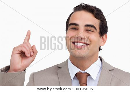 Close up of smiling salesman pointing up against a white background