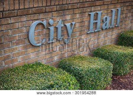 City Hall Sign On A Brick Wall With Low Shrubs