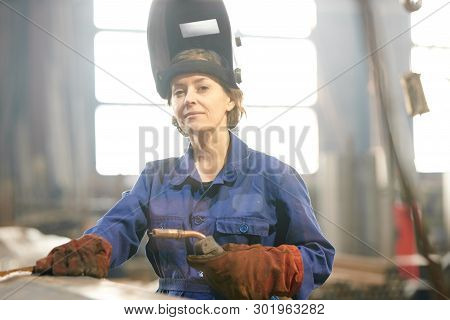 Waist Up Portrait Of Smiling Female Welder Posing Confidently While Working At Industrial Plant Or I