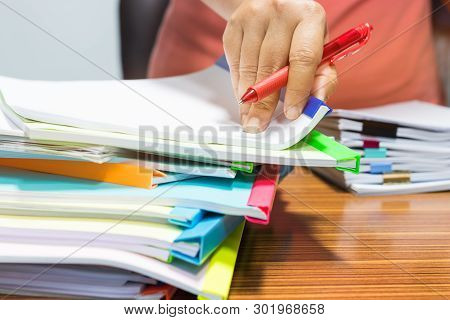 Teacher Hand Holding Red Pen For Checking Report And Students Homework Assignment And Pile Of Unfini