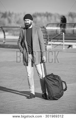 poster of Traveler with suitcase arrive travel destination. Hipster ready enjoy travel. Looking for accommodation. Man bearded hipster travel with big luggage bag wait for taxi bring him to hotel. Travel tips.