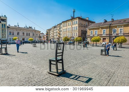 KRAKOW, POLAND - APRIL 19, 2019: Ghetto Heroes Square in Krakow, Poland. The Ghetto Heroes Square is marked by 33 empty chairs. These statues are to commemorate the Jews lost in the Second World War.