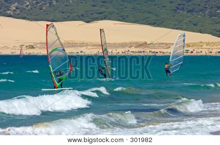 Three Windsurfers On Sandy Tarifa Beach In Southern Spain