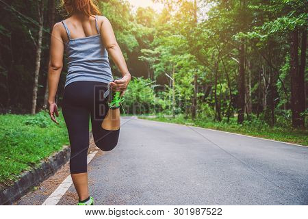 Women Exercise On The Street. Nature Park. Girl Who Is Lifting Legs To Exercise. Exercise, Running.