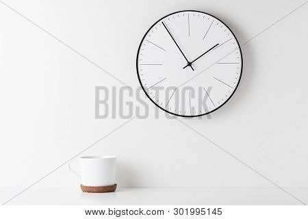 Front View Desk With Round Wall Clock And Cup On White Background. Home Office Minimal Workspace Des