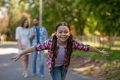 Smiling Little Girl In The Park With Her Arms Open. Girl Has Got Long Pigtails.Parents Are Watching Her Background. poster