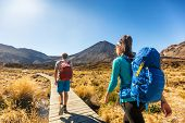 New Zealand Hiking Couple Backpackers Tramping At Tongariro National Park. Male and female hikers hiking by Mount Ngauruhoe. People living healthy active lifestyle outdoors poster