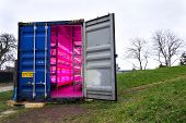 Ready to go shipping container with installed aquaponics, system combines fish aquaculture with hydroponics, cultivating plants in water under artificial lighting poster