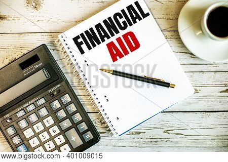 Financial Aid Written On White Paper Near Coffee And Calculator On A Light Wooden Table. Business Co