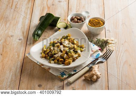 Tofu with zucchini sliced almonds olives turmeric spice and fresh ginger