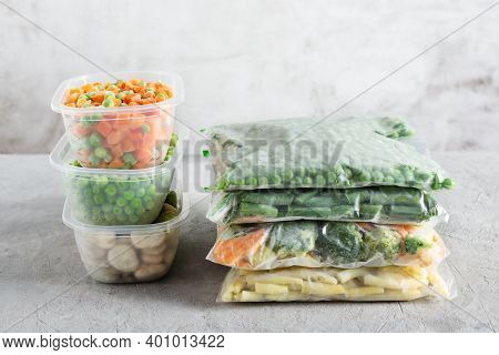 Plastic Containers And Bags With Different Frozen Vegetables.