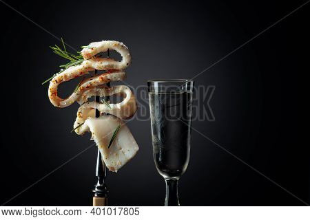 Frozen Glass With Cold Vodka And Slice Of Spicy Salted Lard. Lard With Rosemary On A Dark Background