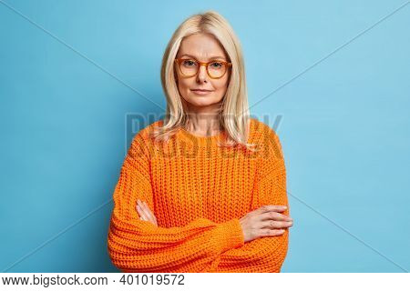 Portrait Of Beautiful Serious Middle Aged Woman Keeps Hands Crossed Wears Spectacles And Orange Swea