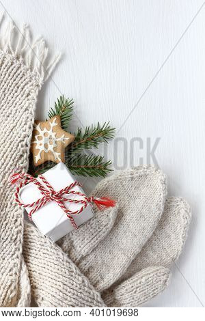 Gift With A White Scarf And Mittens Decorated With A Spruce Branch And A Ginger Star On The Table To