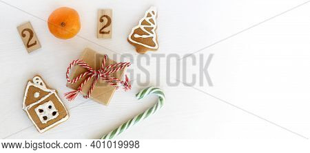 Number 2021, Gift And Striped Candy With Gingerbread House On Long Table Top View. Festive Christmas