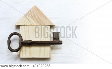 Wooden House And A Large Metal Key On A Light Surface Top View. Weighty Estate Offer