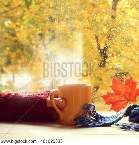 Yellow Cup In Hand On The Background Of The Window After The Autumn Rain. Warming Atmosphere Of Home