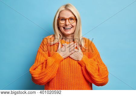 Portrait Of Blonde Female With Cheerful Expression Keeps Hands Pressed To Chest Expresses Gratitude