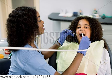 Close Up View Of Little African American Girl Patient Having Dental Treatment At Dentists Office. Fe