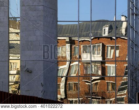 The Mirrored Surface Of The Building Reflects An Old Red Brick Multi-storey Building And Part Of A Y