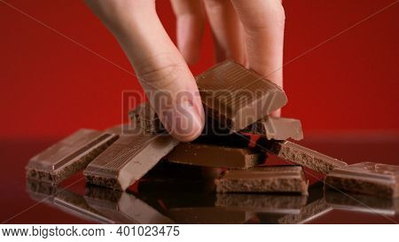 Bunch Of Chocolate Pieces. Stock Footage. Close-up Of Hand Taking Piece Of Chocolate From Pile On Is