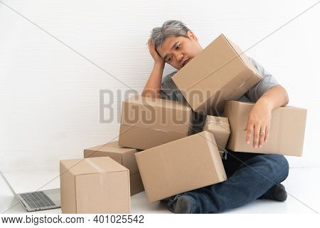 Asian Shopaholic Man Shocked And Sitting On The Floor In The Living Room And Cardboard Box On Top Of