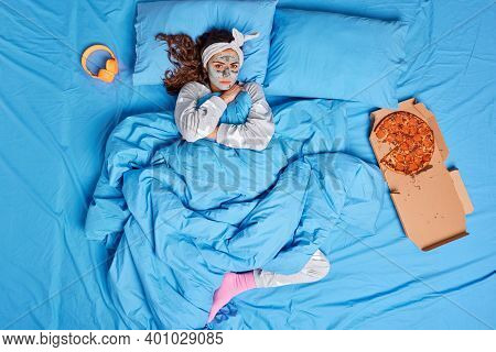 Beautiful Serious Woman With Dark Hair Looks Directly At Camera Poses In Bed With Pizza Enjoys Day O
