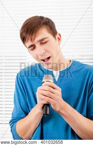 Young Man With A Microphone Sing A Song On The Jalousie Background