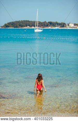 Sexy Woman In Red Swimsuit Standing In Sea Water. Coastline Yacht On Background