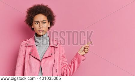 Serious African American Girl Smirks Face Points Away On Copy Space Shows Something Unpleasant Wears
