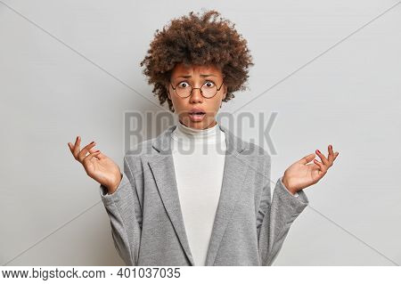 Puzzled Dissatisfied Young Woman With Curly Afro Hair Spreads Palms Sideways Wears Round Spectacles
