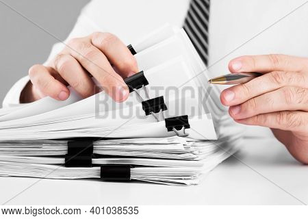 Businessman Hands Working In Stacks Of Paper Files For Searching Information On Work Desk Home Offic
