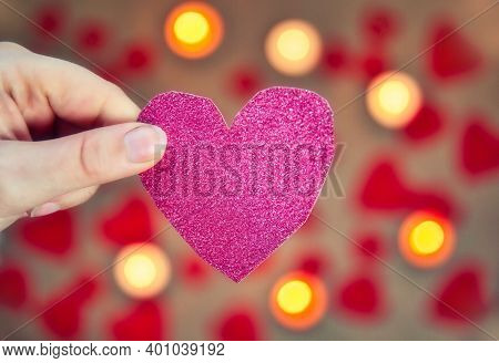 Female Hand Holding A Glitter Pink Heart With Romantic Candle And Red Hearts Background For Valentin