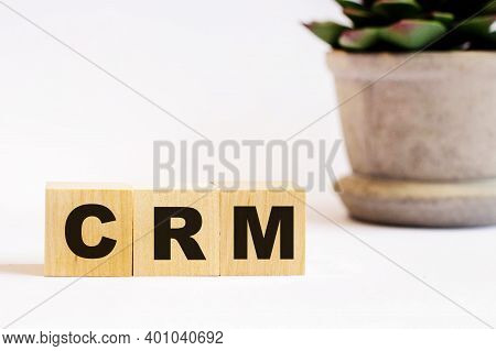 On A Light Background, Wooden Cubes With The Inscription Crm Crm Customer Relation Management And A