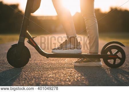 Close Up Of Woman Riding Electric Kick Scooter At Sunset. Electric Urban Transportation
