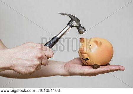 A Man About To Break Open A Ceramic Piggy Bank With A Large Hammer. Piggy Bank Is About To Be Hit By
