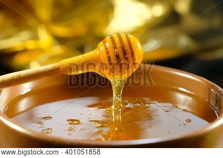 Honey Drips From The Honey Dipper In A Bowl. Healthy Organic Thick Honey Dipping From A Wooden Honey