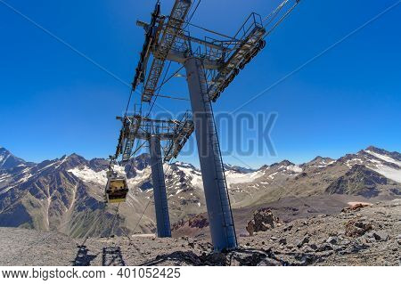 Cable Car Cabin Over A Precipice In The Mountains. Travel By Cable Car In The Caucasus Mountains To