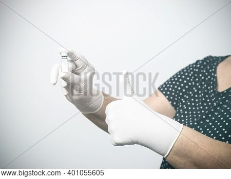 Lady Holding Vaccine Ampoule In Hand With Gloves And Doing Ok With Fingers