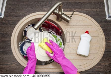 Close Up Hands Of Woman Washing Dishes In Kitchen. Hands In Red Rubber Gloves Washing The Dishes. To