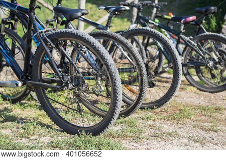 Variety Of Bicycles Offered For Rent Are In The Parking Lot. View On The Wheels Of Bicycles In Row.