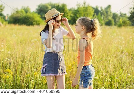 Children Are Having Fun In Nature. Two Girls Laugh, Look At Themselves In The Mirror Of Sunglasses,