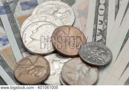 Various Paper Banknotes Dollars And Metal Coins Cents. American Coins Of Various Denominations Lie O