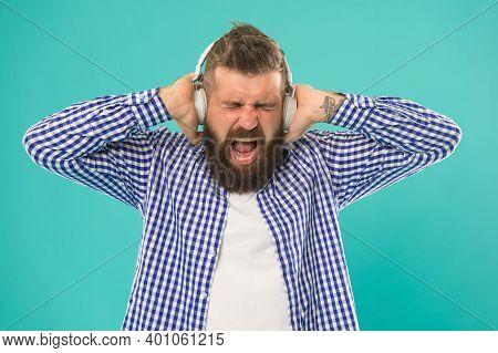 Listening Heavy Metal. Unhappy Bearded Man With Loud Sound In Earphones. Caucasian Guy With Beard An